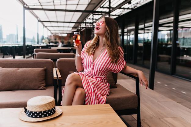 여름 날에 와인을 마시는 동안 웃 고 멋진 금발 백인 소녀. 아늑한 카페에서 포즈를 취하는 스트라이프 드레스에 사랑스러운 여성 모델의 사진. 무료 사진