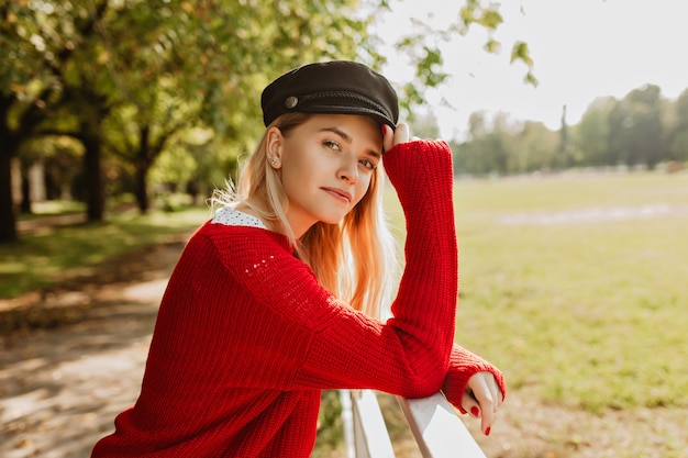 Stunning blonde enjoying sunny weather outdoor. pretty girl in trendy red pullover looking good in the autumn park. Free Photo