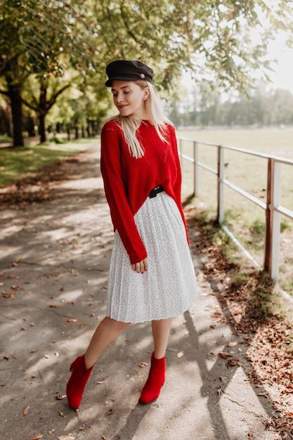 トレンディな赤いセーターとダークな素敵な帽子のスタイリッシュなドレスを着ている見事なブロンド。落ち葉の間で自信を持ってポーズをとる美しいモデル。 無料写真