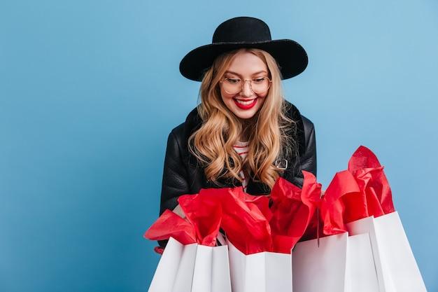쇼핑백을 들고 멋진 금발 여자입니다. 파란색 벽에 포즈 우아한 모자에 웃는 소녀. 무료 사진