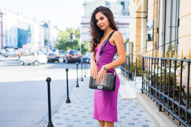 日当たりの良い通りを歩いて、晴れた天候を楽しんで、買い物をして、週末に素晴らしい時間を過ごすために友達を待っている美しいブルネットの少女。ウェーブのかかった髪型。紫色のベルベットのセクシーなドレス。ロマンチックな気分。 無料写真