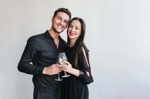 Splendida donna bruna tintinnio di bicchieri con bel marito durante la festa di un amico Foto Gratuite