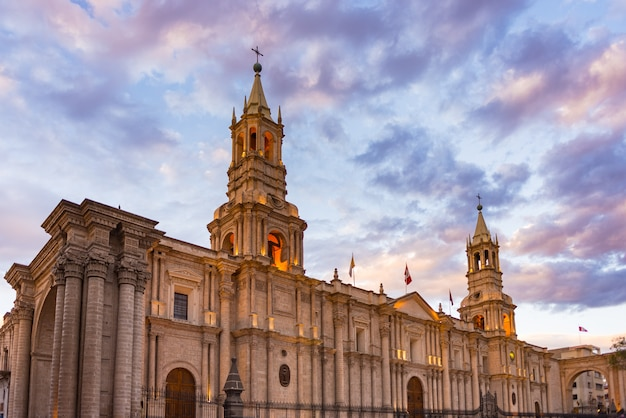 Stunning colorful sky and clouds at dusk in arequipa, famous travel destination and landmark in peru. wide angle view from below of the colonial cathedral. panoramic frame. Premium Photo