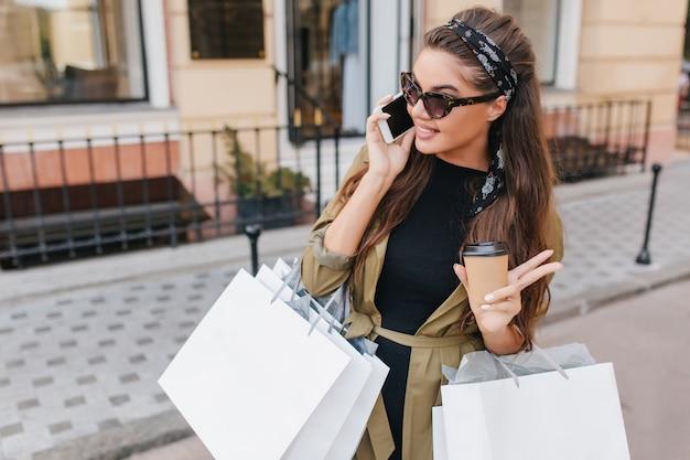 Splendida donna alla moda dai capelli scuri parla al telefono in una giornata di sole che trasporta grandi pacchetti dalla boutique Foto Gratuite