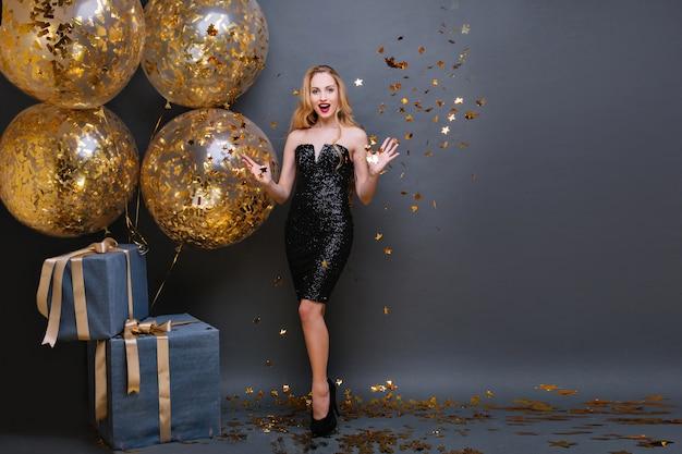 Splendida donna europea bionda che lancia coriandoli scintillanti mentre posa. adorabile ragazza di compleanno caucasica in piedi con grandi scatole regalo e agitando le mani con un sorriso. Foto Gratuite