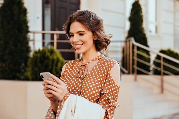 興味のある表情で携帯電話の画面を見ているエレガントなブラウスの見事な女性モデル。笑顔で茶色の服装のテキストメッセージメッセージで喜んでいるヨーロッパの女性の屋外ショット。 無料写真