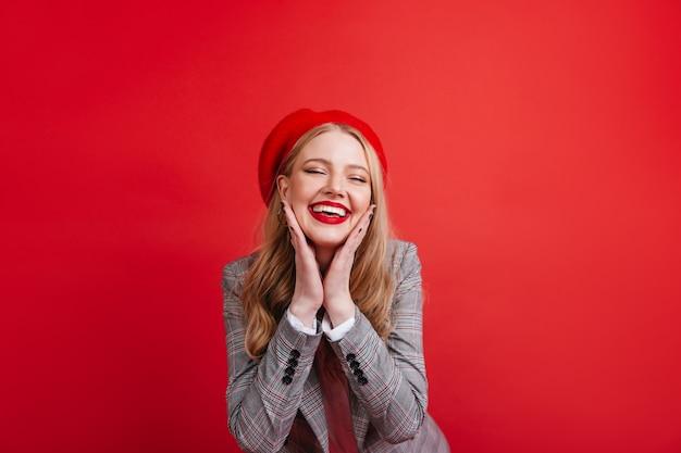 빨간 벽에 포즈를 취하는 멋진 프랑스 소녀. 웃 고 기쁜 금발의 젊은여자가 무료 사진