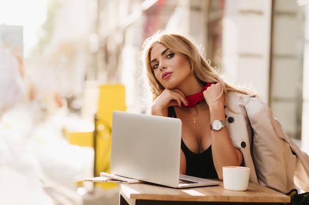 見事な女性がネックレスを身に着けており、カフェでラップトップを使用して作業中に腕時計がカメラに見える 無料写真