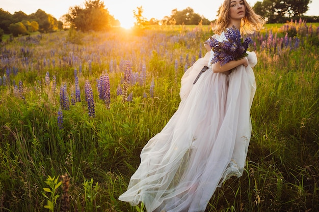 Stunning lady in white dress stands with bouquet on the field Free Photo