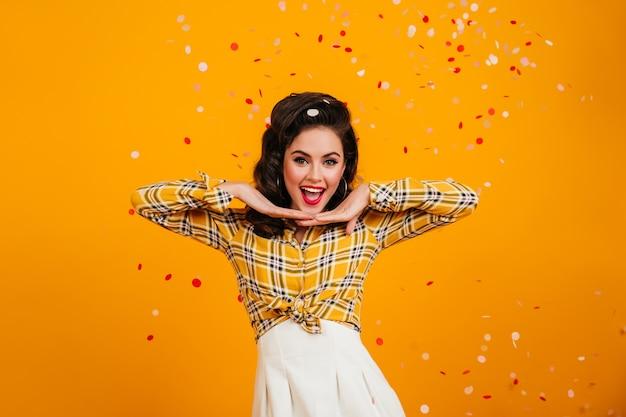 긍정적 인 감정을 표현하는 멋진 핀업 소녀. 색종이 아래 포즈 체크 무늬 셔츠에 사랑스러운 갈색 머리 여자의 스튜디오 샷. 무료 사진