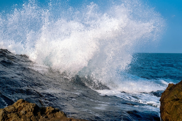 Stunning shot of crazy powerful sea waves crashing the rock formations Free Photo