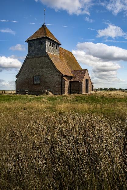 Splendida ripresa di una vecchia chiesa e di un campo erboso nel regno unito in una giornata nuvolosa Foto Gratuite