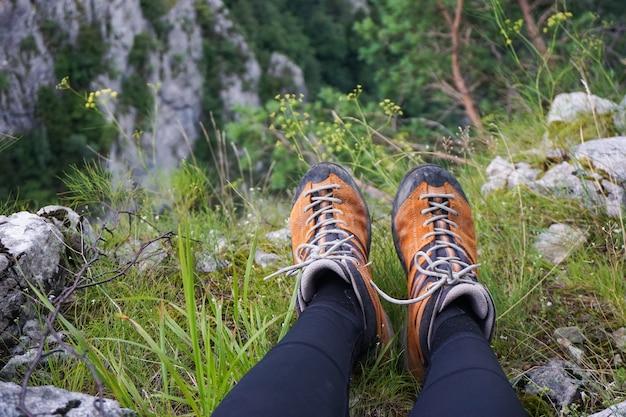Colpo sbalorditivo di una persona seduta su un terreno di rocce erbose e fiori in un campeggio Foto Gratuite