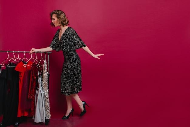 Потрясающая стройная девушка в модной обуви стоит возле вешалок и выбирает наряд Бесплатные Фотографии