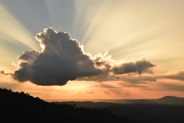The stunning sun beams from the clouds in the sunset sky. Premium Photo