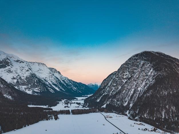 日没時に寒くて雪の日の山脈の素晴らしい景色 無料写真