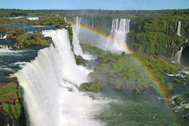 Stunning view of powerful iguazu falls  from brazilian side with a gorgeous rainbow Premium Photo