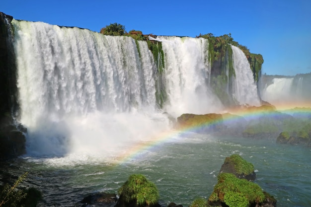 Stunning view of the powerful iguazu falls with beautiful rainbow, foz do iguacu, brazil Premium Photo