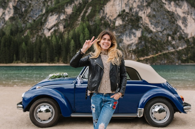 Stunning woman in denim pants and knitted jersey gladly posing beside blue car during trip around italy Free Photo