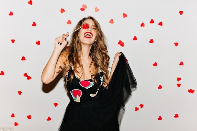Потрясающая женщина смеется с закрытыми глазами и играет со своим платьем Бесплатные Фотографии