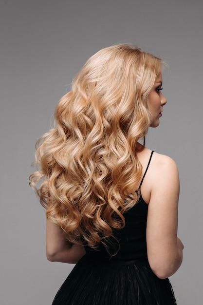 完璧なウェーブのかかったブロンドの髪を持つ見事な女性。 Premium写真
