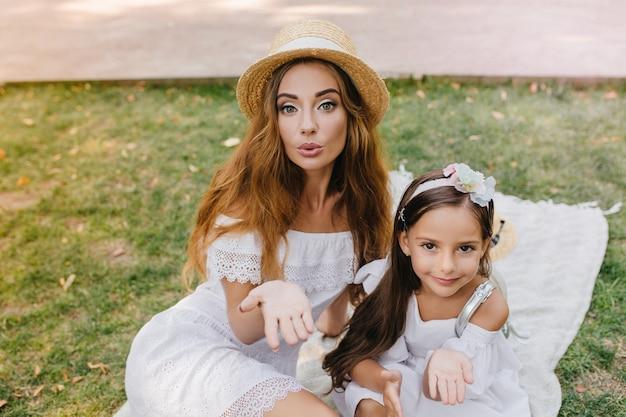 ピクニックで写真を撮る世界と愛を共有する見事な若い女性とかわいい女の子。朝、芝生でリラックスしたエアキスを送る、似たような白い服を着た2人の素晴らしい姉妹。 無料写真