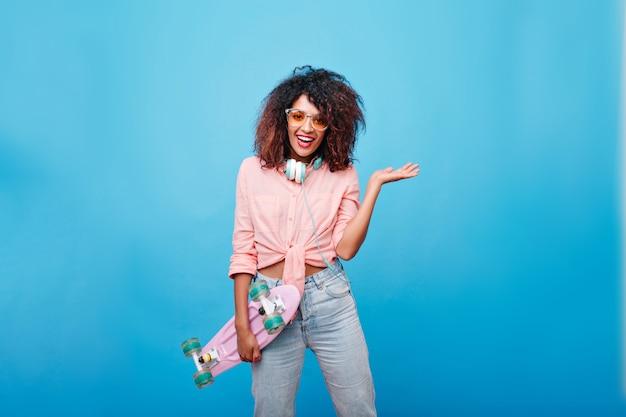 誠実な笑顔でポーズをとるサングラスをかけたジーンズとピンクのシャツを着た見事な若い女性。スケートボードを持って笑っているイヤホンで巻き毛のかわいいアフリカの女の子。 無料写真