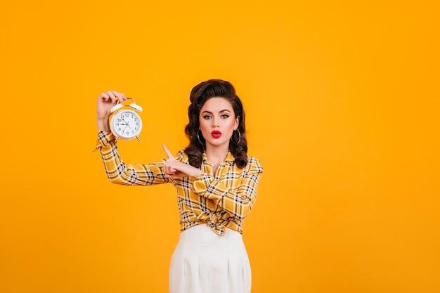 시계와 함께 포즈를 취하는 밝은 화장과 멋진 젊은 여자. 노란색 배경에 고립 된 매력적인 핀 업 소녀의 스튜디오 샷. 무료 사진