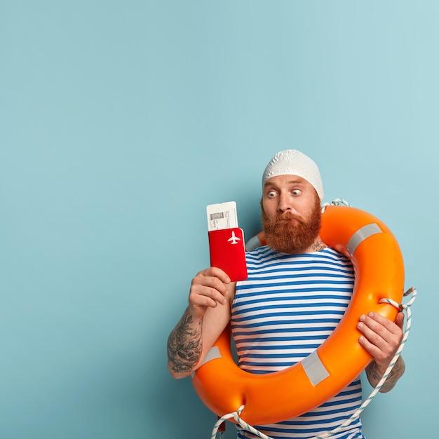 髭を生やした男がパスポートと航空券に衝撃を与えて見つめ、夏休みにリゾート地での飛行機の旅の準備をします 無料写真