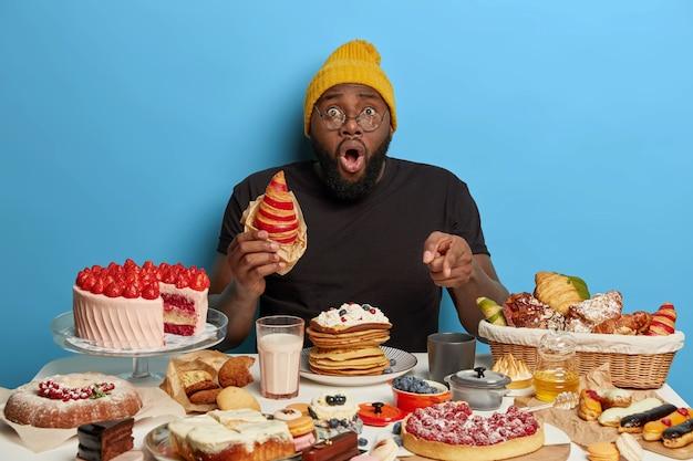 Ошеломленный темнокожий мужчина ест вкусный круассан, показывает на стол, полный сладких вкусных десертов, носит шляпу и футболку, позирует на синем фоне Бесплатные Фотографии