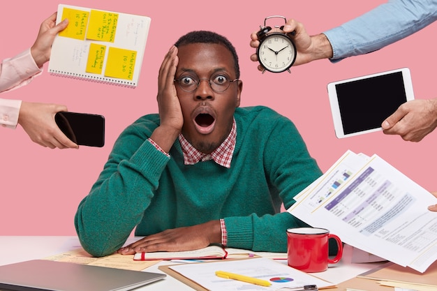 Stupefied dark skinned guy opens mouth from fear, expresses great surprisement and wonder, being overload with much paper work Free Photo
