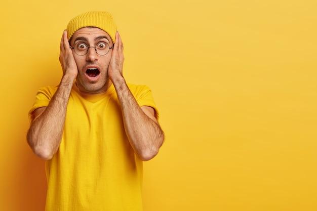 Un uomo europeo stupefatto e emotivo tiene le mani sul viso, la bocca ampiamente aperta, non può credere a una rilevanza scioccante, indossa vividi abiti gialli, è molto emotivo. omg concetto Foto Gratuite