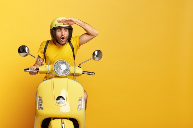 Stupefied guy with helmet driving yellow scooter Free Photo