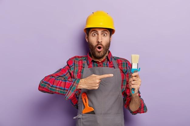 Stupefatto lavoratore manuale indica l'attrezzo di riparazione, impegnato nella ricostruzione, indossa l'elmetto protettivo, un'uniforme speciale. operaio edile sorpreso dimostra al pennello, essendo al lavoro. ristrutturazione Foto Gratuite