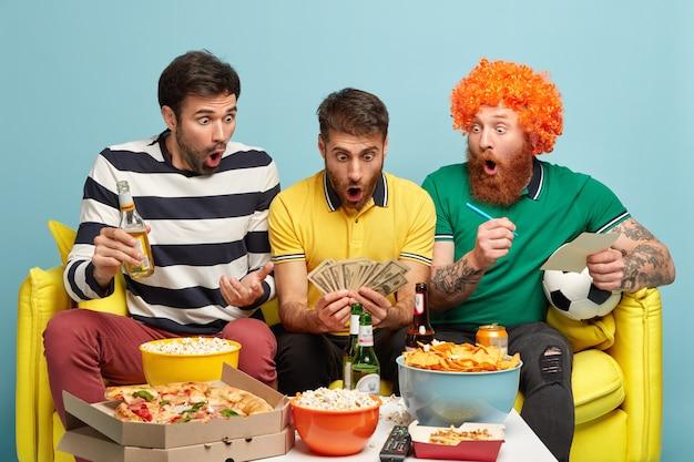Gli uomini stupiti guardano sorprendentemente i contanti, entusiasti di vincere una scommessa, guardare la partita di calcio in televisione, coinvolti nel gioco d'azzardo, mangiano fast food. ragazzo emotivo con un sacco di soldi, goditi la lega dei campioni Foto Gratuite