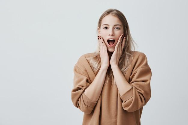 Ошеломленная блондинка ошеломлена, широко раскрывает рот Бесплатные Фотографии