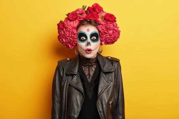 ゴースト塗装の顔、レースの黒いドレス、革のジャケット、赤い花で作られた花輪が色の背景の上に立っていると愚かな恐怖の女性 無料写真