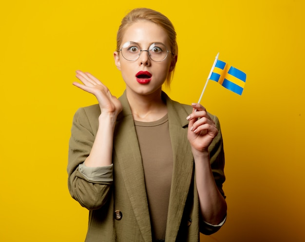 Style blonde woman in jacket with swedish flag on yellow Premium Photo