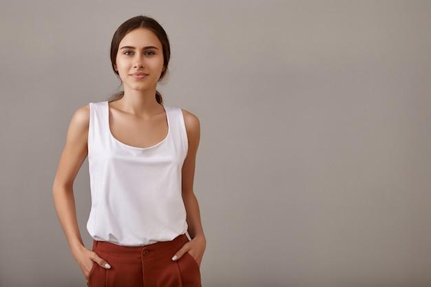 스타일, 패션, 우아함 및 자신감 개념. 주머니에 그녀의 손을 유지, 빈 Copyspace 벽에 고립 된 포즈 맨 손으로 그을린 어깨와 세련 된 젊은 유럽 여자 무료 사진