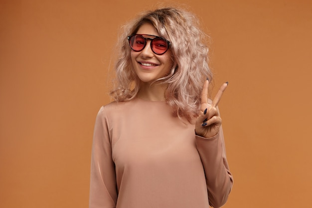 Style, fashion trends and youth concept. picture of fashionable hipster girl wearing trendy sunglasses with pink lenses  with joyful broad smile, making peace sign Free Photo