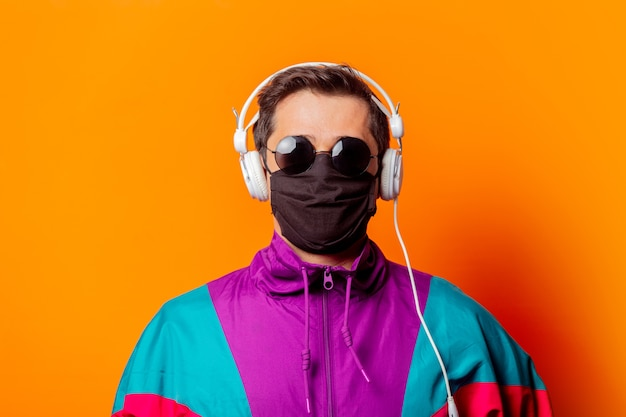 Style man in face mask and 80s tracksuit with headphones Premium Photo