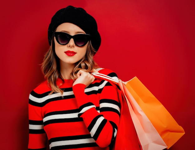 Style woman in sunglasses with shopping bags on red wall Premium Photo