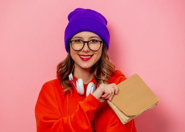 Style woman with headphones and books on pink wall Premium Photo