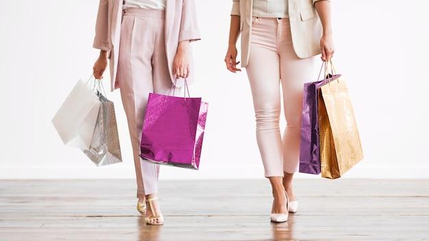 Donne adulte alla moda che trasportano i sacchetti della spesa Foto Gratuite