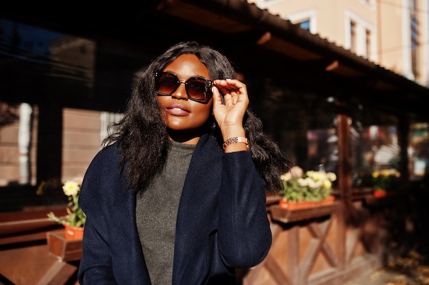 Stylish african american girl in blue coat and sunglasses posed at sunny autumn day. africa model woman. Premium Photo