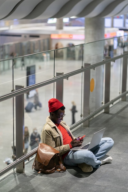 Stylish african american traveler millennial man resting and sitting on the floor in airport, using cellphone. Premium Photo