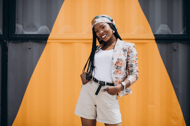 Stylish african american woman by the colored wall Free Photo