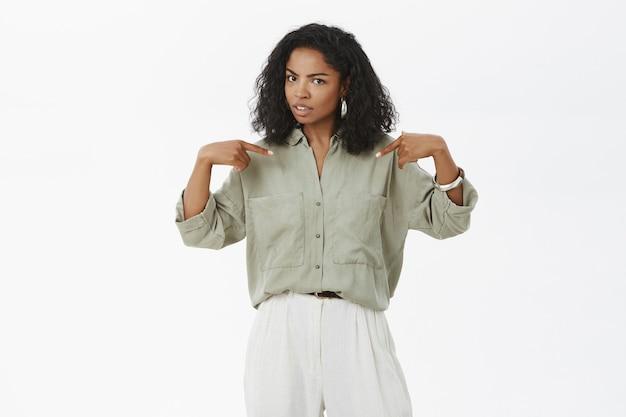 Elegante donna afro-americana che punta a se stessa con espressione incerta Foto Gratuite