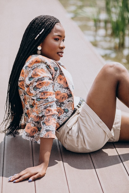 Stylish african american woman sitting by the lake in the park Free Photo