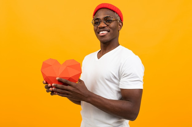 Stylish african man with a beautiful snow-white smile in a white t-shirt holds out a red 3d mock-up of a heart made of paper for valentine's day and look sideways at the yellow studio Premium Photo